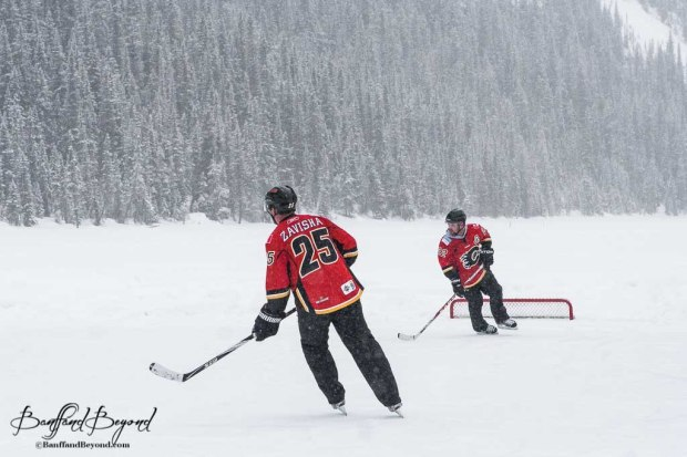 two-people-playing-pond-hockey-on-lake-louise